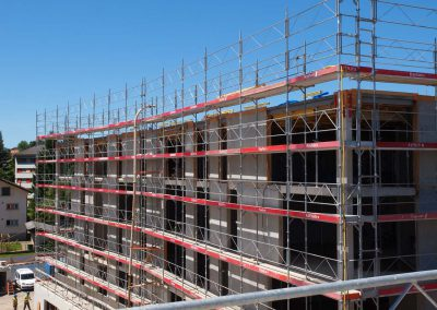 Montage d'échafaudages sur un chantier de construction à Bulle